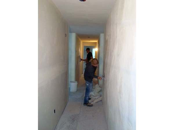 Jackson and Curtis apply American Clay plaster to the hallway walls.